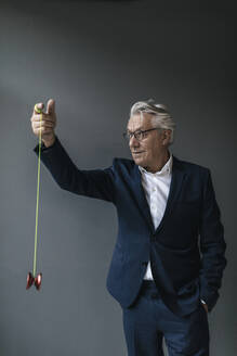 Senior businessman playing with yoyo - GUSF02550
