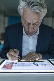 Senior businessman drawing on shining tablet - GUSF02559