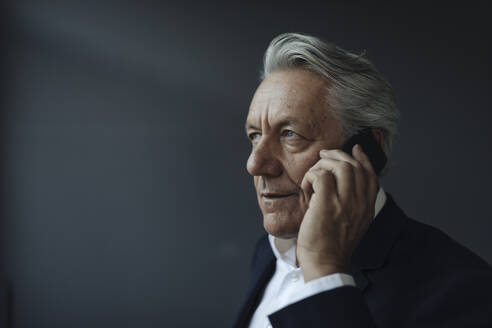 Portrait of a senior businessman talking on cell phone - GUSF02580