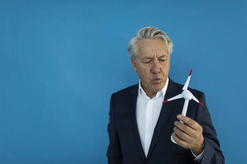 Senior businessman holding wind turbine model - GUSF02592