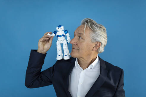 Senior businessman with robot on his shoulder - GUSF02595
