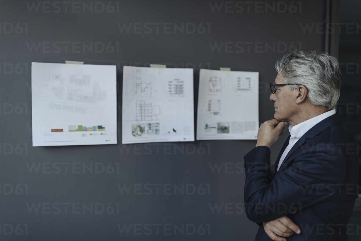 Senior businessman looking at papers hanging on the wall - GUSF02613 - Gustafsson/Westend61