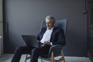 Senior businessman sitting in armchair using laptop - GUSF02616