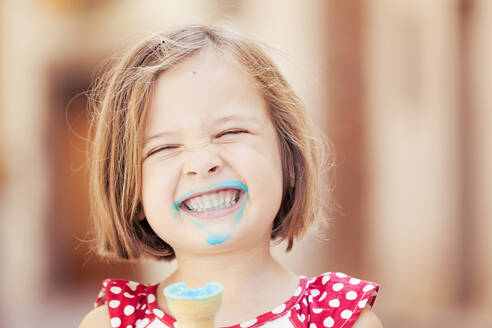 A happy girl eating a blue ice cream - XCF00213