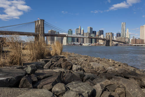 Brooklyn Bridge over East river against blue sky in New York City, USA - XCF00216