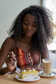 Portrait of young African woman eating a piece of cake and having a coffee - VEGF00700