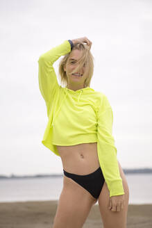 Portrait of blond young woman posing on the beach wearing neon yellow sweatshirt and black bikini pants - JESF00289