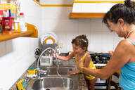 Little girl and grandmother playing with water in the kitchen - GEMF03140