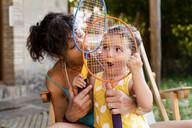 Grandmother playing with little girl and badminton rackets outdoors - GEMF03143