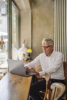 Senior businessman using laptop in a cafe - GUSF02621