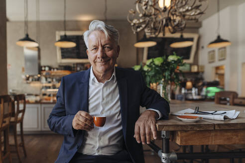 Portrait of senior businessman drinking espresso in a cafe - GUSF02627