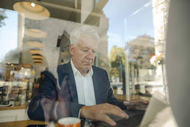 Senior businessman using laptop in a cafe - GUSF02633