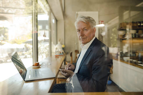 Portrait of senior businessman with cell phone and laptop in a cafe - GUSF02636