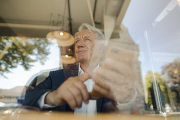 Senior businessman using cell phone in a cafe - GUSF02639