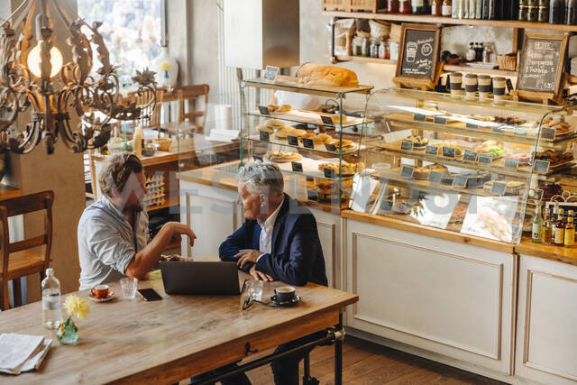 Two businessmen with laptop meeting in a cafe - GUSF02651 - Gustafsson/Westend61