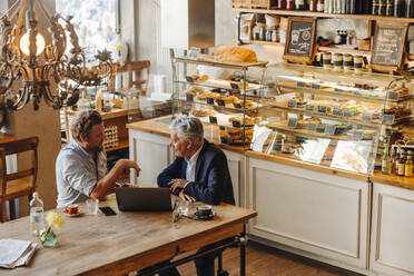 Two businessmen with laptop meeting in a cafe - GUSF02651