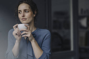 Portrait of young woman relaxing with cup of coffee - KNSF06552