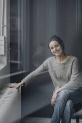 Portrait of smiling young woman sitting next to heater at home - KNSF06582