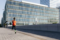 Young man jogging in the city, listening to music - JRFF03709
