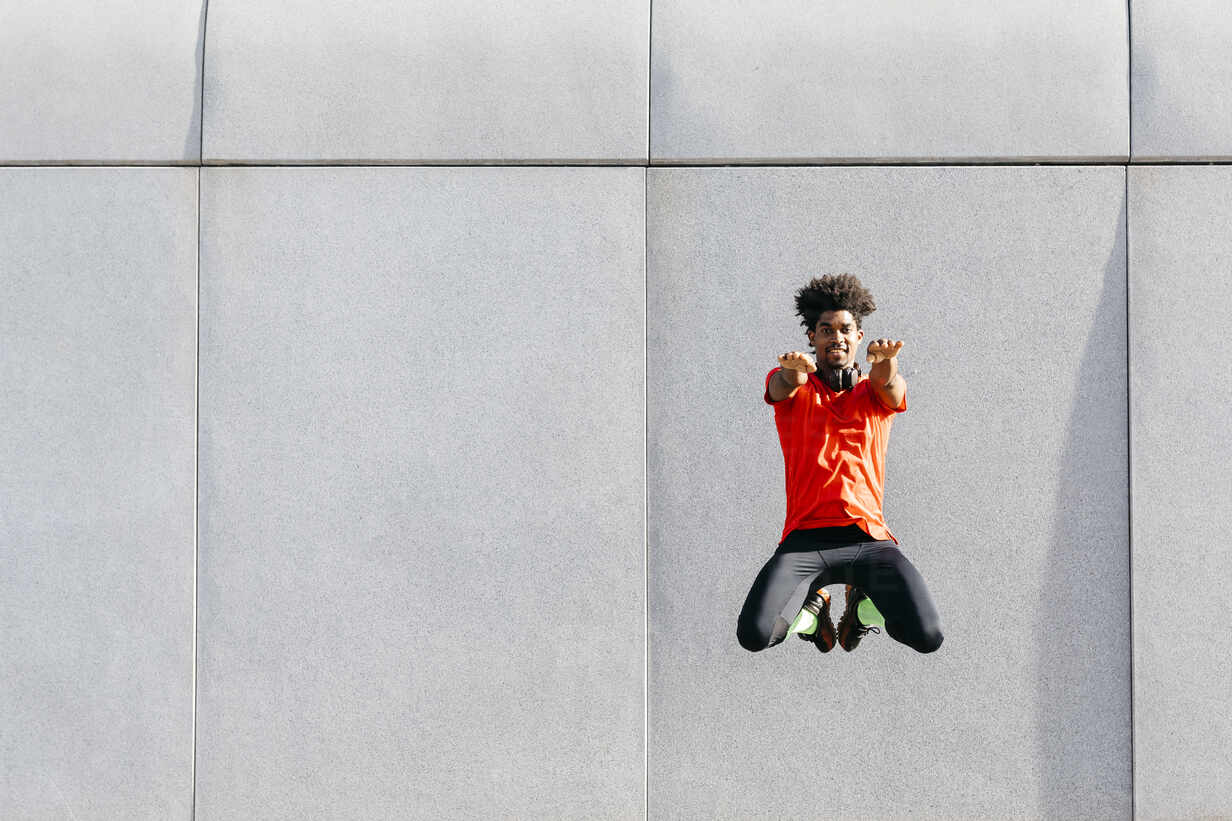 Young man doing jumps with a gray wall in the background - JRFF03739 - Josep Rovirosa/Westend61