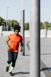 Young man jogging in the city, listening to music - JRFF03742