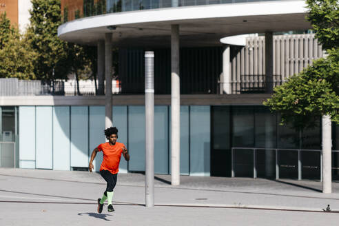 Young man jogging in the city, listening to music - JRFF03745