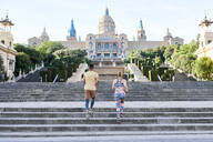 Man and woman running on stairs at Palau Nacional, Barcelona, Spain - JNDF00085