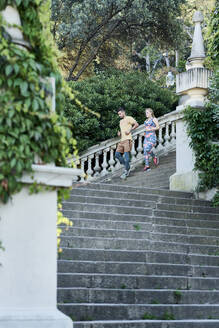 Man and woman running down stairs - JNDF00088