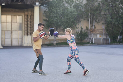 Fitness coach practicing boxing class with young woman outdoors in the city - JNDF00097