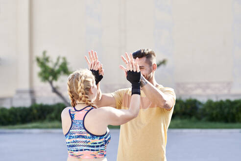 Man and woman finishing workout outdoors in the city - JNDF00100