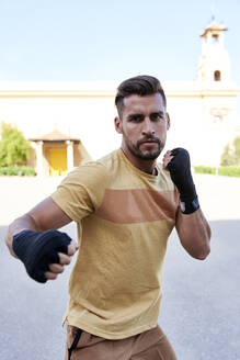 Man doing boxing exercise outdoors in the city - JNDF00106