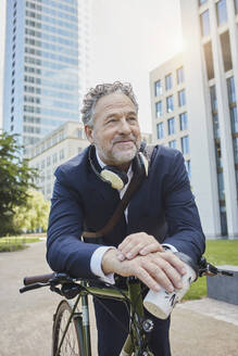 Mature businessman with bicycle and takeaway coffee in the city - RORF01850