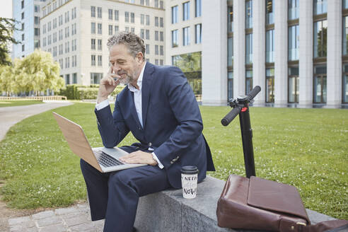 Mature businessman sitting on a wall in the city using laptop - RORF01853