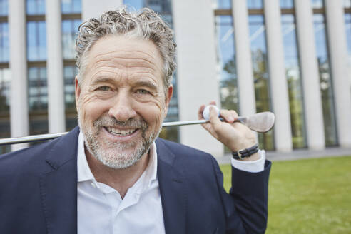 Portrait of happy mature businessman with golf club in the city - RORF01859