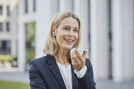 Smiling businesswoman using smartphone in the city - RORF01865