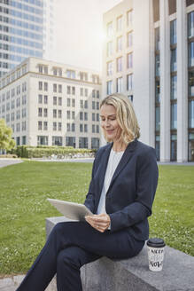 Businesswoman sitting on a wall in the city using tablet - RORF01871