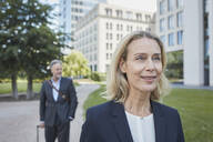 Porrait of smiling blond businesswoman in the city with businessman in background - RORF01880