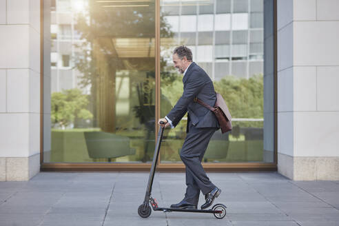 Businessman on e-scooter passing office building in the city - RORF01886