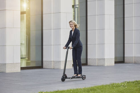 Businesswoman on e-scooter passing office building in the city - RORF01889