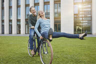 Exuberant mature couple riding bicycle on lawn in the city - RORF01922