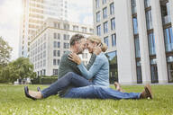 Happy mature couple cuddling on lawn in the city - RORF01928