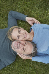 Top view of happy mature couple lying in grass - RORF01931