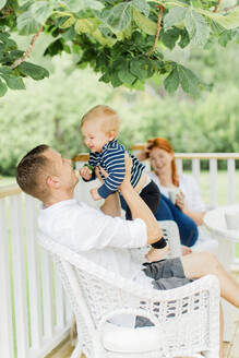 Parents with baby boy resting on balcony - JOHF00500