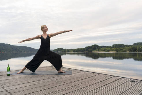 Young woman practicing yoga on a jetty at a lake - JOSF03590