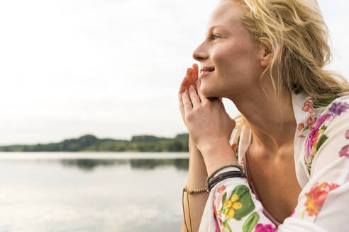 Portrait of smiling young woman at a lake - JOSF03593