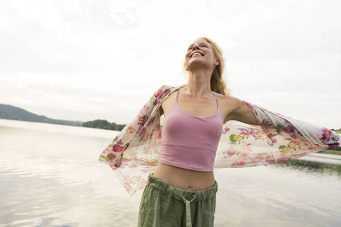 Happy young woman at a lake - JOSF03596