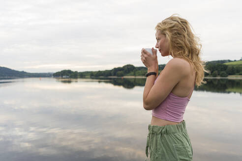 Young woman drinking coffee from cup at a lake - JOSF03602