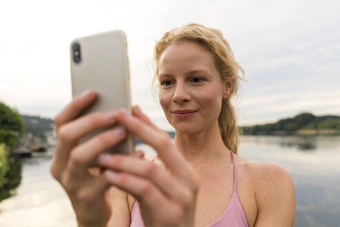Young woman using cell phone at a lake - JOSF03608