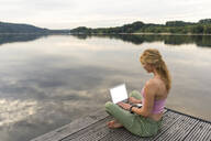Young woman using laptop on a jetty at a lake - JOSF03611