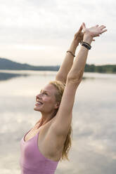 Happy young woman raising her arms at a lake - JOSF03617